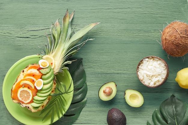 Bovenaanzicht op ananasboten met gerookte zalm en avocadoplakken met citroen en kwartelseieren