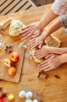 Bovenaanzicht op bijgesneden moeder dochter tonen hoe deeg voor taart of koekjes uitrollen, klein schattig kind kind leren muffins verbiedt kookproces met gelukkige moeder in lichte keuken