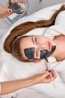 Bovenaanzicht op bijgesneden professionele schoonheidsspecialist die een zwart masker toepast op een fris gezicht van een mooie ontspannen blanke vrouw voor koolstofschil. huidverzorging, welzijn, spa, beauty concept. ruimte kopiëren