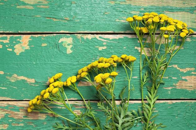 Bovenaanzicht op bloemen van boerenwormkruid op een oude houten tafel