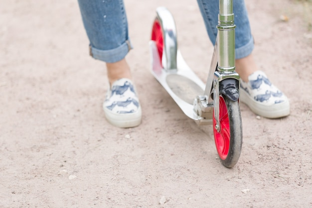 Bovenaanzicht op dames voeten in sneakers op de scooter in het park
