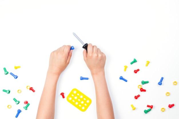 Bovenaanzicht op de handen van kinderen spelen met kleurrijke speelgoed tools op witte achtergrond
