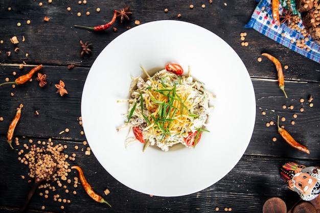 Bovenaanzicht op de salade van rundvleesreepjes met groenten en spaanders op de zwarte houten lijst