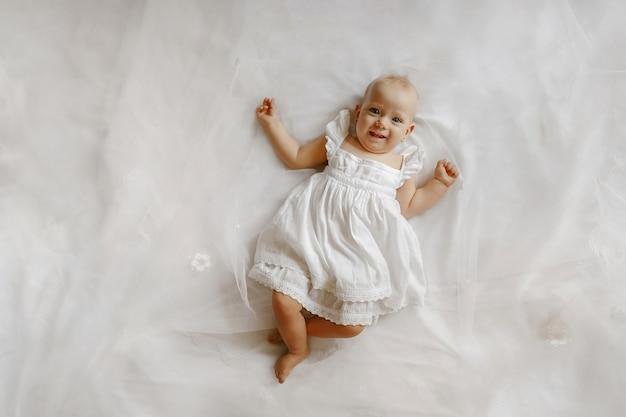 Bovenaanzicht op de schattige vrouwelijke baby die op het bed ligt