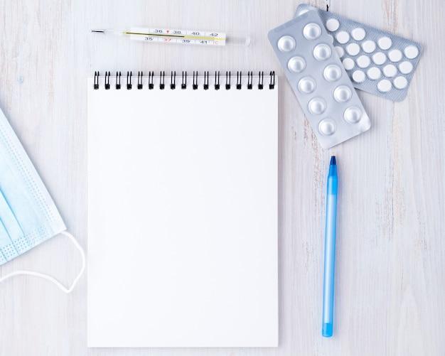 Bovenaanzicht op de tafel in het kantoor van de dokter. open blocnote met een blanco pagina, een medicijn, een pen