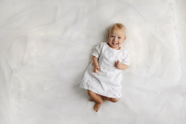 Bovenaanzicht op de vrouwelijke kleine baby die op het bed ligt