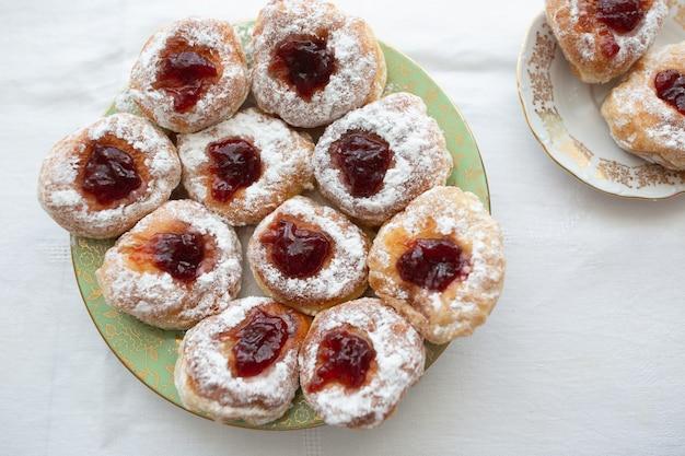 Bovenaanzicht op een bord donuts gevuld met jam en bedekt met suiker.