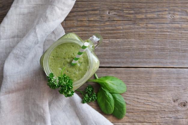 Bovenaanzicht op een glas groene smoothie en spinazieblaadjes op hout