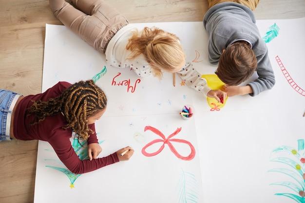 Bovenaanzicht op een multi-etnische groep kinderen tekenen van afbeeldingen op de vloer terwijl ze genieten van kunstles op kerstmis, kopieer ruimte