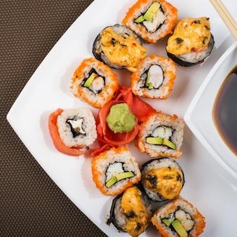 Bovenaanzicht op een schotel van verschillende sushi in een witte plaat