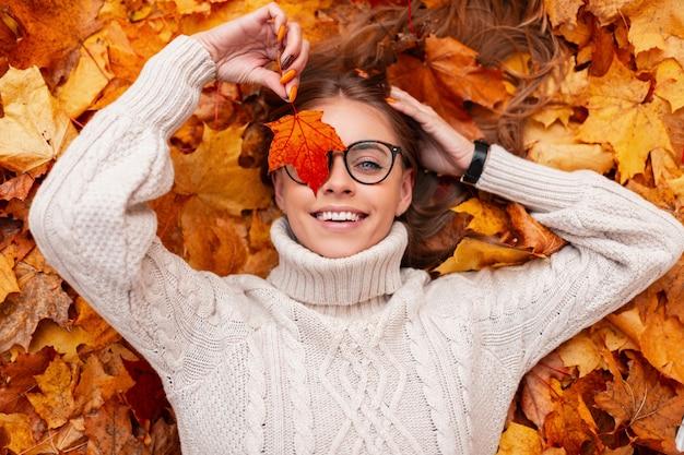 Bovenaanzicht op een vrolijke jonge vrouw in een stijlvolle bril in een gebreide witte trui met een oranje blad in de buurt van het gezicht in het park op een achtergrond van gouden gebladerte. leuk gelukkig meisje ligt in het bos.