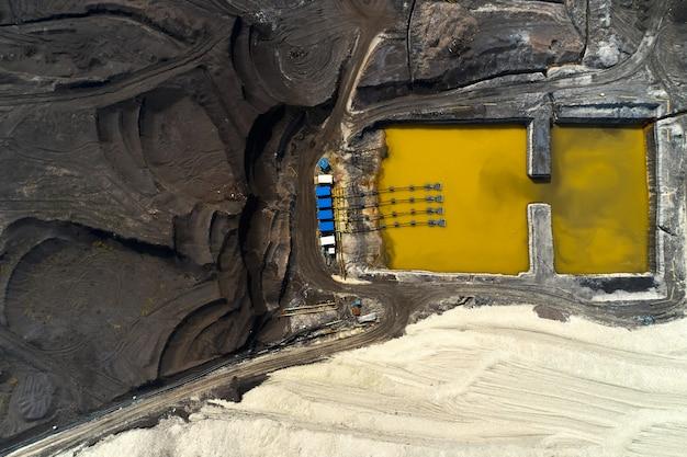 Bovenaanzicht op een zwembad met gele vloeistof gebruikt in een mijnbouw in een steengroeve