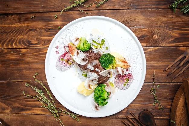 Bovenaanzicht op gastronomisch ingerichte schotel met rundvlees op de houten tafel