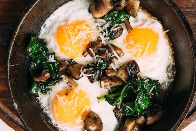 Bovenaanzicht op gebakken eieren met champignons en spinazie in gietijzeren pan