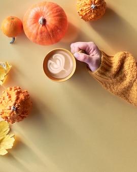 Bovenaanzicht op geel herfst stilleven met latte in keramische mok op geel papier. geel papier plat lag met de hand met een kopje koffie, oranje pompoenen, kweepeer en een paar canvas sneakers.