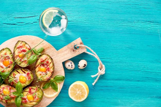 Bovenaanzicht op gegrilde avocadoboten met spek en ei