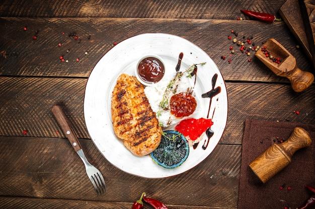 Bovenaanzicht op gegrilde gastronomische kipfilet steak met rijst