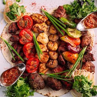 Bovenaanzicht op gegrilde vleesschotel met groenen en saus