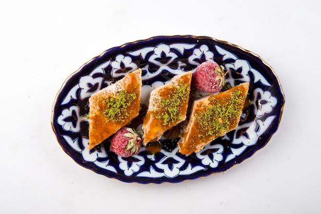 Bovenaanzicht op geïsoleerde oosterse zoetheid baklava met honing en pistachenoten op de traditionele plaat