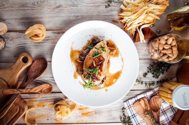 Bovenaanzicht op gekookte kipfilet op champignons op de houten tafel
