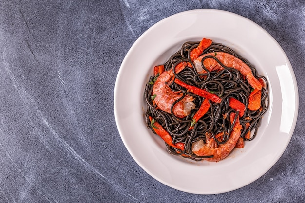 Bovenaanzicht op gekookte zwarte pasta met garnalen