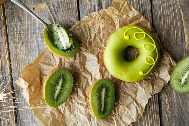 Bovenaanzicht op groene donut met gesneden kiwi