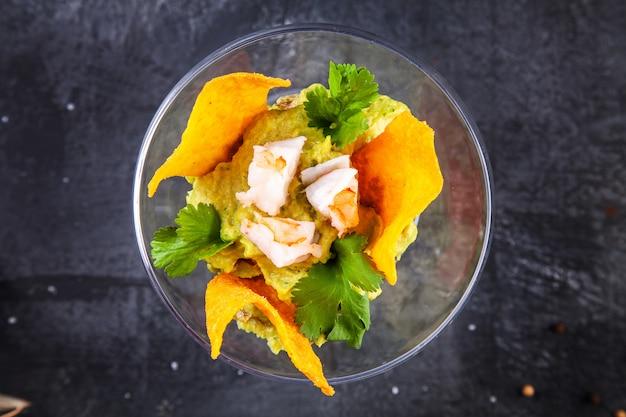 Bovenaanzicht op guacamole met nacho's en garnalen in glas op donker