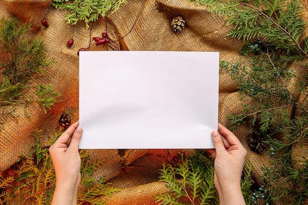 Bovenaanzicht op handen met papier met feestelijke spar