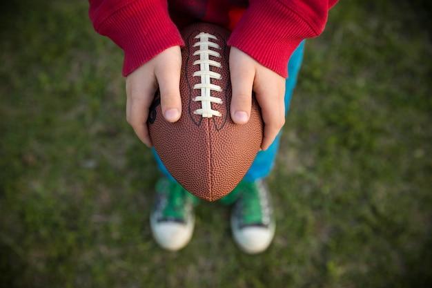 Bovenaanzicht op handen van kleine jongen die op een zonnige dag voetbal op het stadion houdt