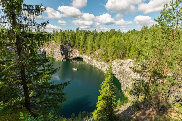 Bovenaanzicht op het meer met de toeristenboot in marble canyon, ruskeala, karelië.