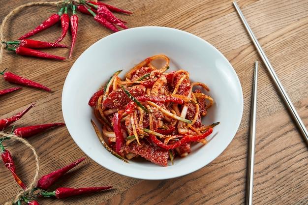 Bovenaanzicht op hoe traditionele koreaanse gerechten, zoetzure auberginesalade met vis in keramische kom op houten oppervlak. plat gelegd voedsel. veganistische groentesalade