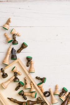 Bovenaanzicht op houten schaakcijfers op witte tafelachtergrond