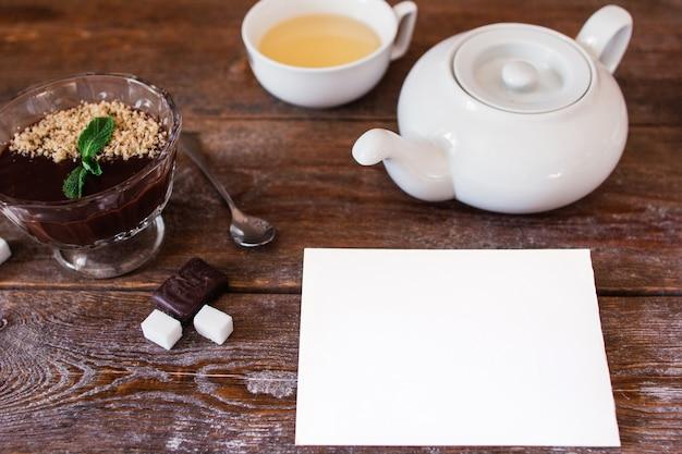 Bovenaanzicht op houten tafel met set voor het drinken van thee en chocoladeroom met wit leeg vel papier, vrije ruimte