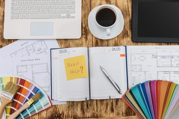 Bovenaanzicht op huisplan en laptop met kleurenmonster