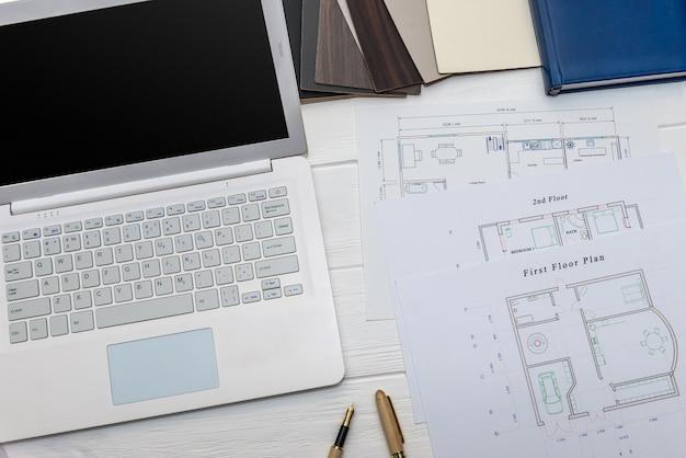 Bovenaanzicht op huisplan en laptop met rekenmachine