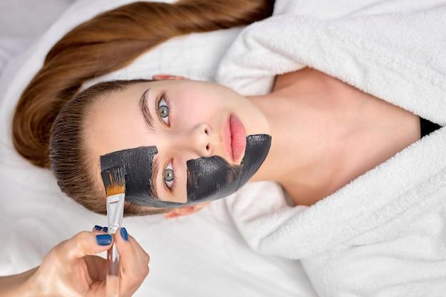 Bovenaanzicht op jonge aantrekkelijke vrouw in spa salon met zwart masker op gezicht, kopieer ruimte