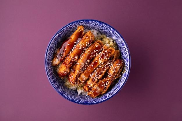 Bovenaanzicht op katsudon gebakken kip met rijst in een kom