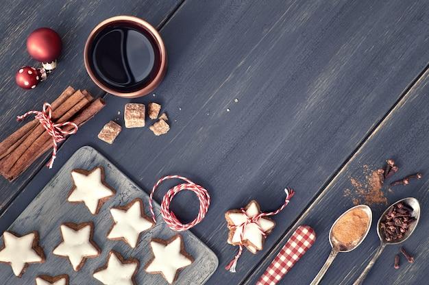 Bovenaanzicht op kerstkoekjes, glühwein, specerijen en decoraties