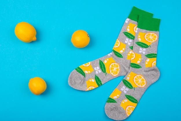 Bovenaanzicht op kleurrijke paar sokken en citroenen fruit geïsoleerd op blauw oppervlak