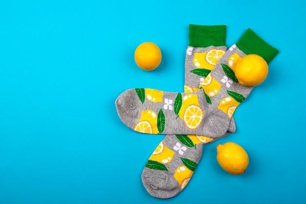 Bovenaanzicht op kleurrijke paar sokken en citroenen op blauwe ondergrond