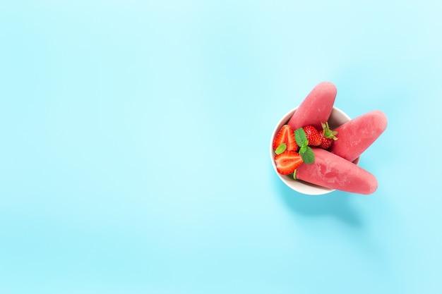 Bovenaanzicht op kom met fruitig roze bevroren sorbetijs op plastic stokje met aardbei, munt op blauwe achtergrond. bevroren gemengd fruit met yoghurt in de vorm van ijs. kinderen eten het graag