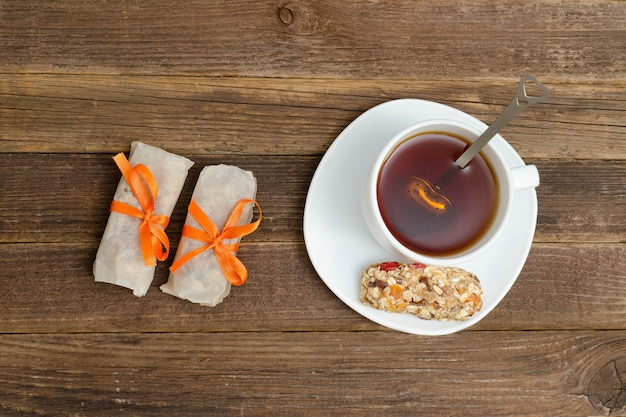 Bovenaanzicht op kopje thee en enkele reep muesli. bruine houten tafel