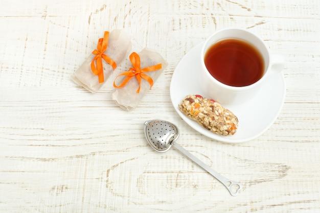 Bovenaanzicht op kopje thee en enkele reep muesli. witte houten achtergrond