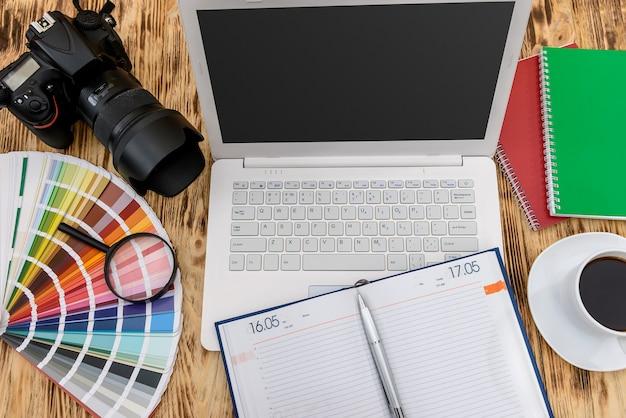 Bovenaanzicht op laptop, camera en dagboek