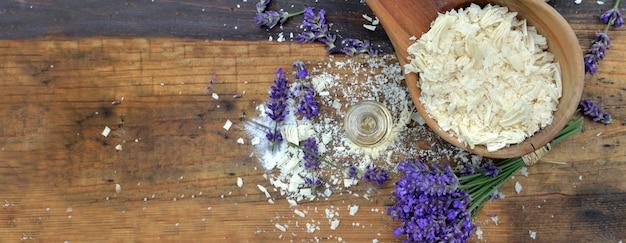 Bovenaanzicht op lepel vol zeepvlokken met etherische olie en lavendelbloemen op houten tafel