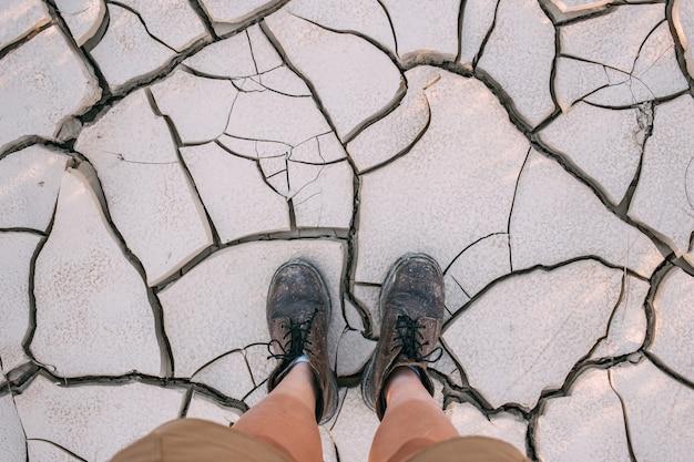 Bovenaanzicht op leren laarzen op gebarsten droge aarde