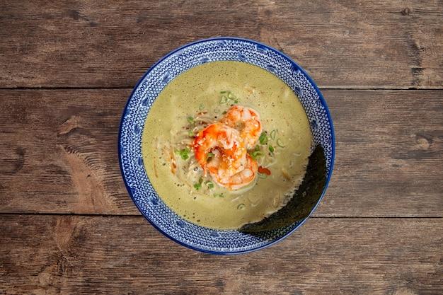 Bovenaanzicht op matcha ramen-soep met langoustines