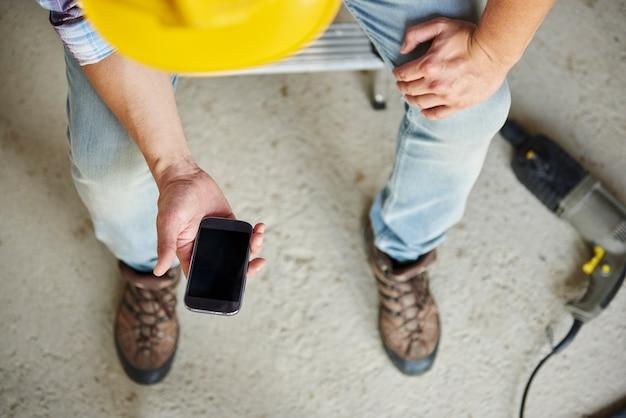 Bovenaanzicht op mobiele telefoon die wordt gebruikt door handarbeider