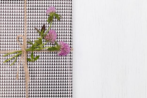 Bovenaanzicht op mooi cadeau verpakt in geruit papier en versierd met klaver op witte houten achtergrond
