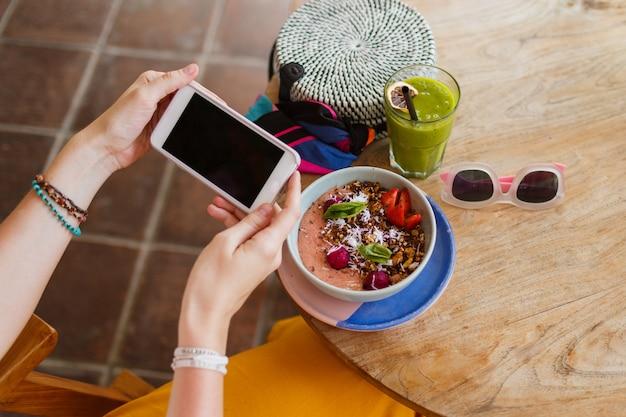 Bovenaanzicht op mooie vrouw in gele broek met behulp van telefoon en genieten van lekker veganistisch eten